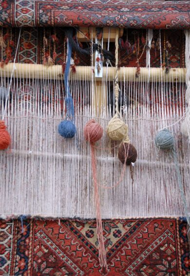 A vertical or upright loom showing the partly woven rug the warp threads and balls of wool yarn Image Shutterstock