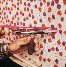 Close up of an Indian weaver using a hand tufting gun to make a rug cheaply and faster than hand knotting Image NC Larsen